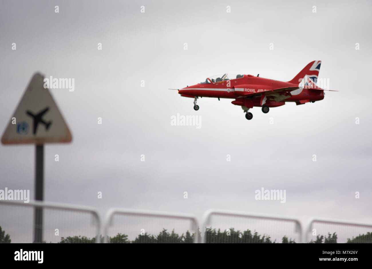 red arrows jet aircraft on landing with low flying aircraft triangular warning  road sign - Stock Image