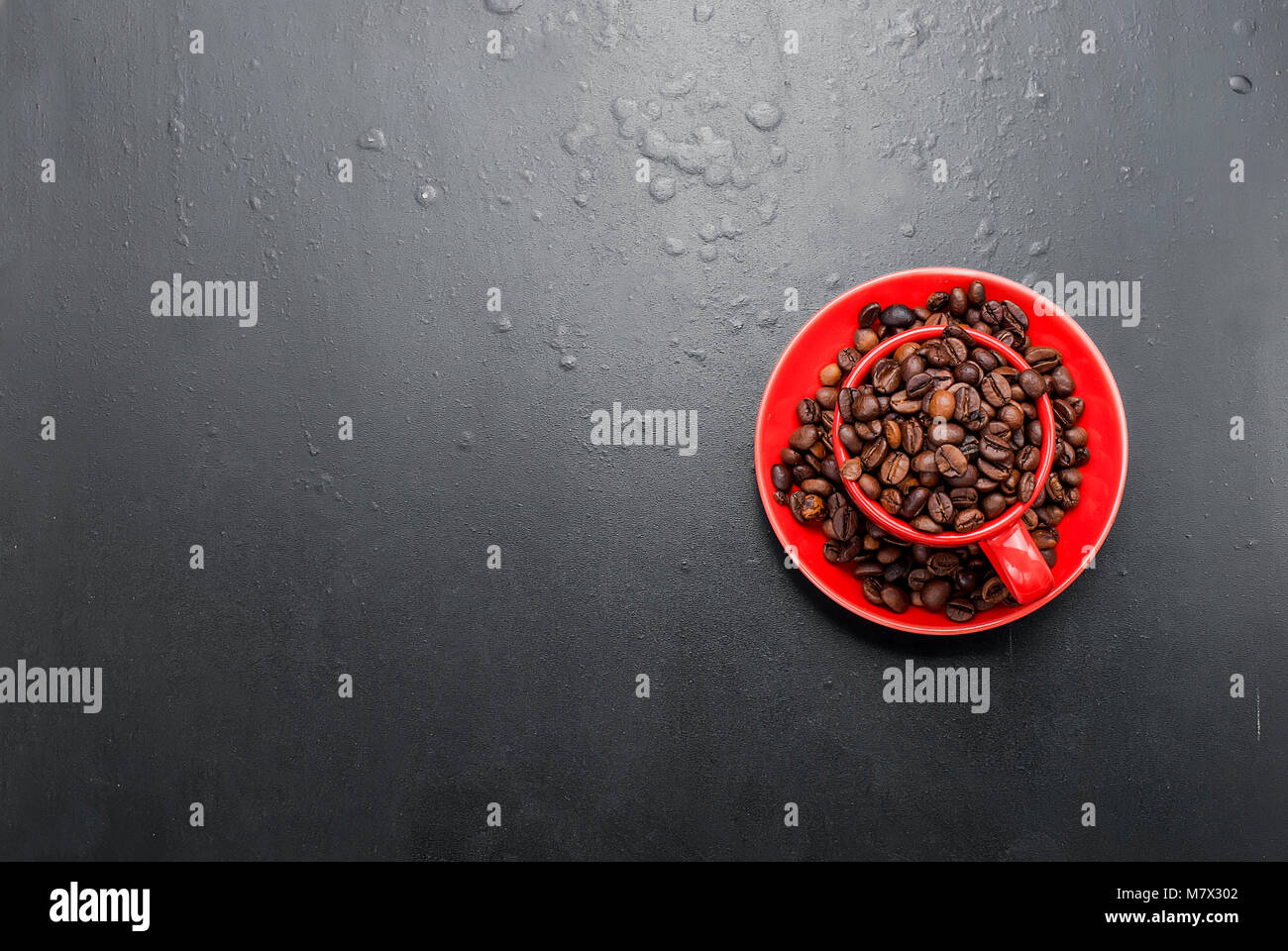 red cup  and coffee beans on a black background, top view , copy space - Stock Image