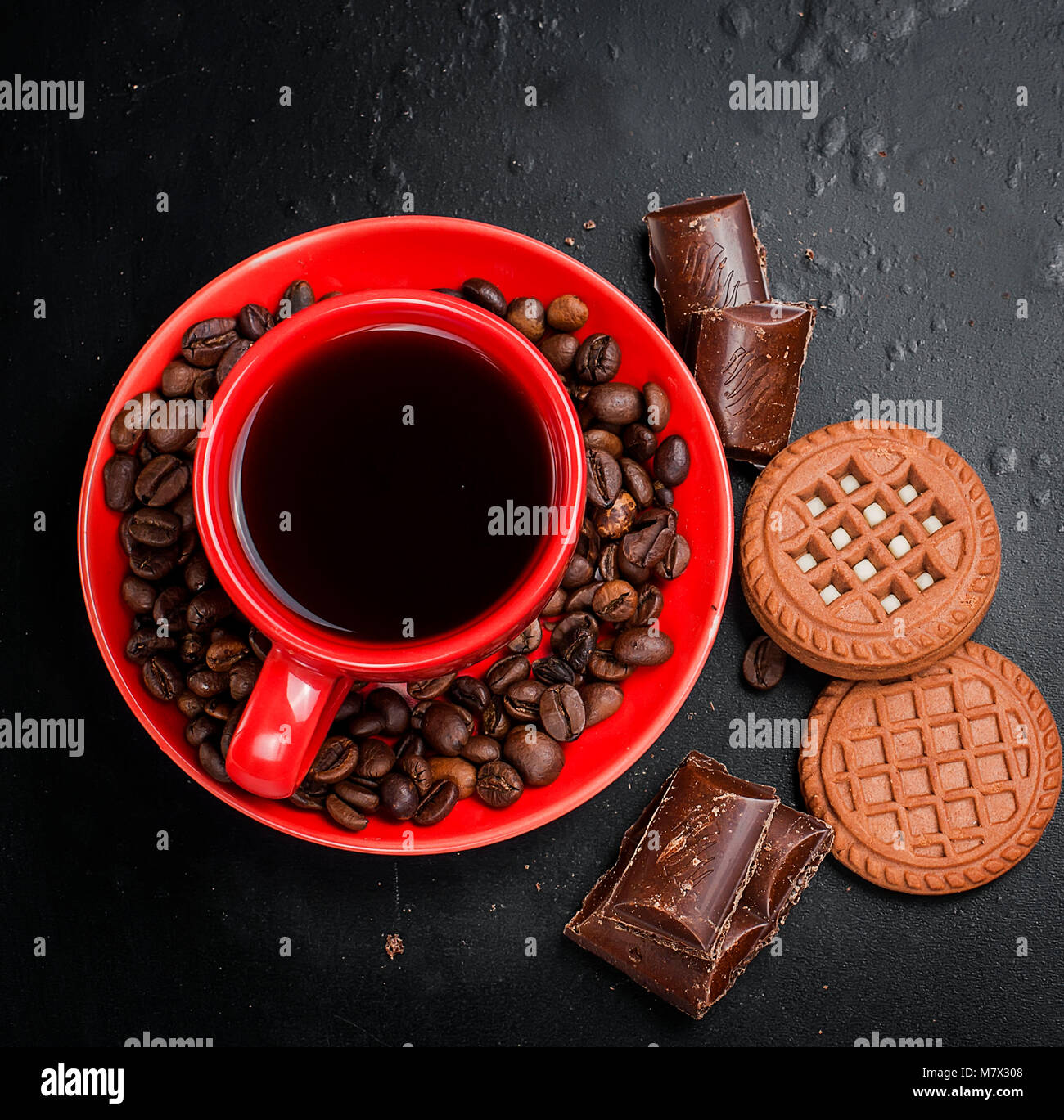 red cup of hot strong coffee with chocolate cookies and pieces of dark chocolate and coffee beans on a black background, - Stock Image