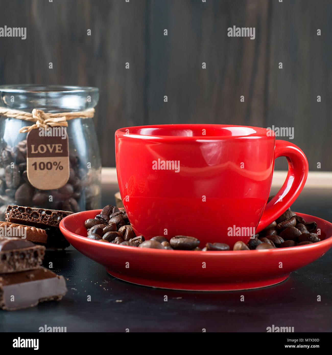 red cup of hot strong coffee with chocolate cookies and pieces of dark chocolate and coffee beans on a black background - Stock Image