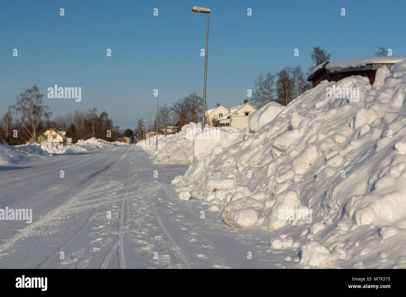 Road through an little village in the winter with a lot of snow of both sides and a blue sky in background, picture - Stock Image