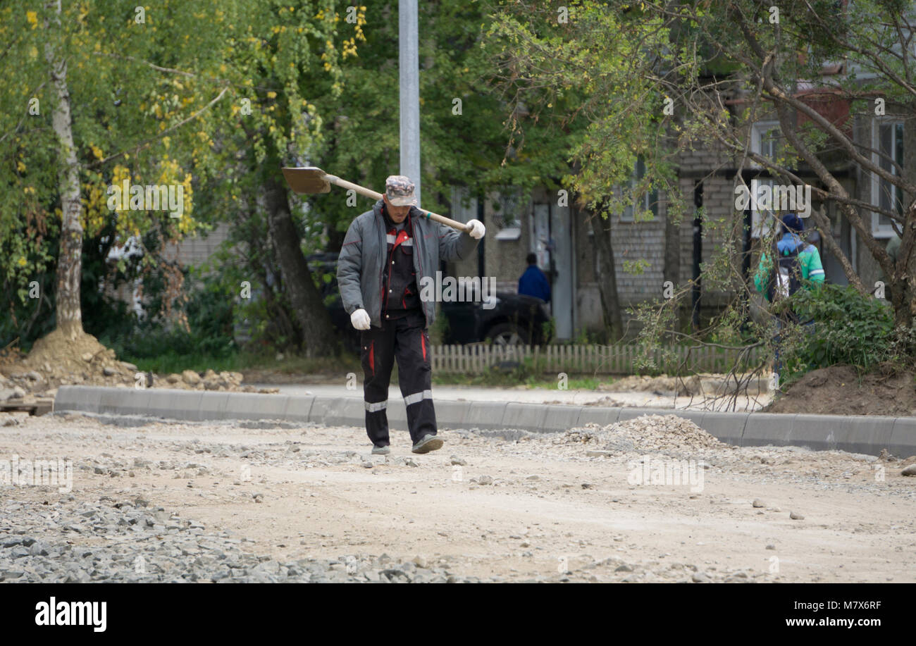 male holding shovel and looking at sky Russia Berezniki 4 September 2017 - Stock Image
