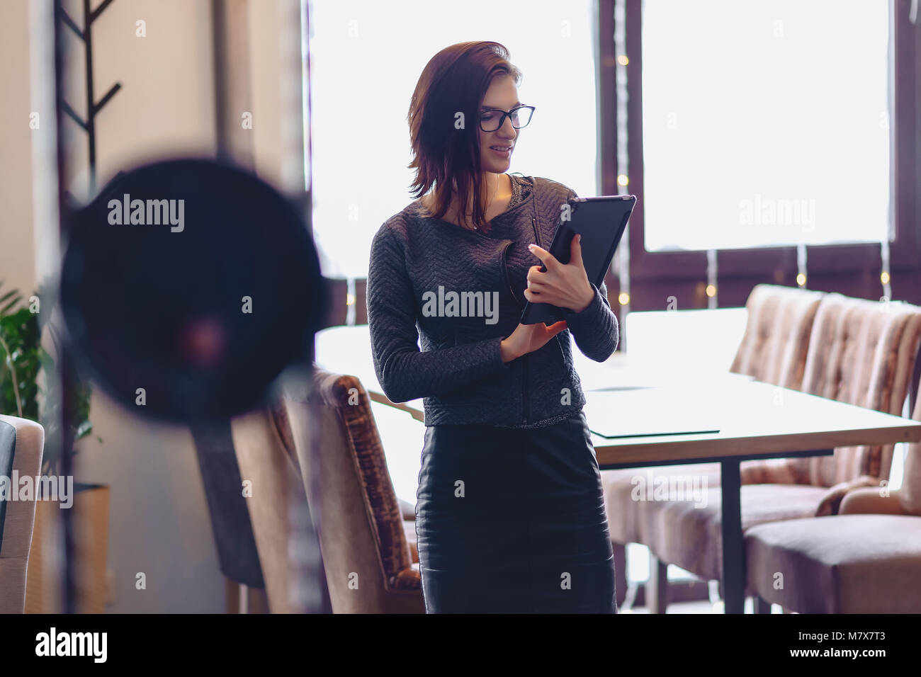 The girl in the glasses is standing with a tablet at the bars at the cafe Stock Photo
