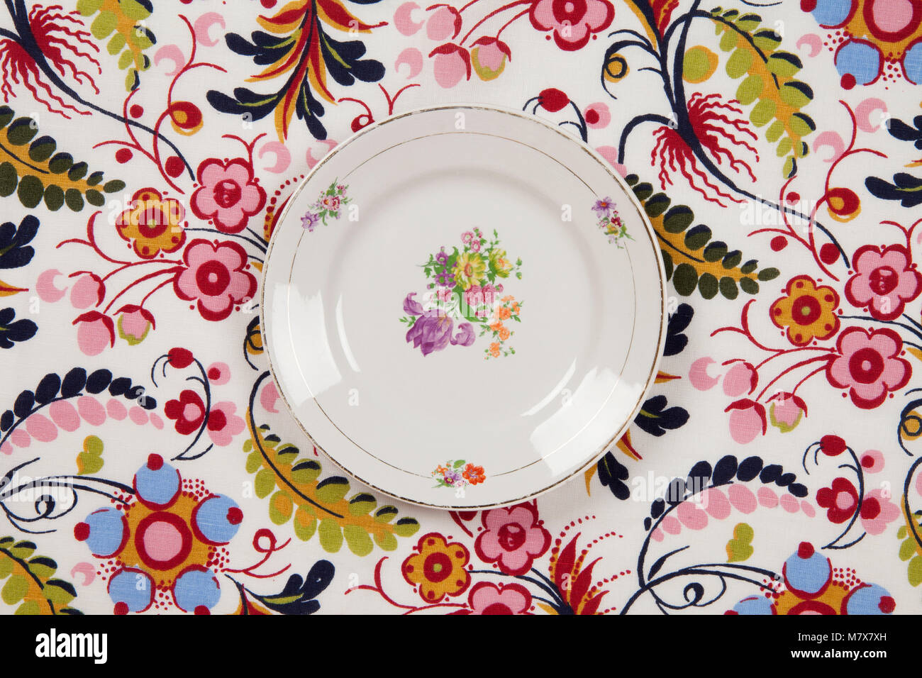 a flower plate hidden on a flowery fabric. Camouflage game. Minimal color still life photography. Stock Photo