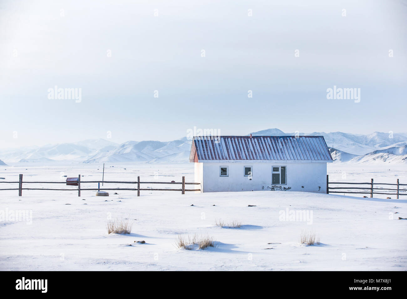 small white house in a snow covered valley in the middle of mountains of Northern Mongolia Stock Photo