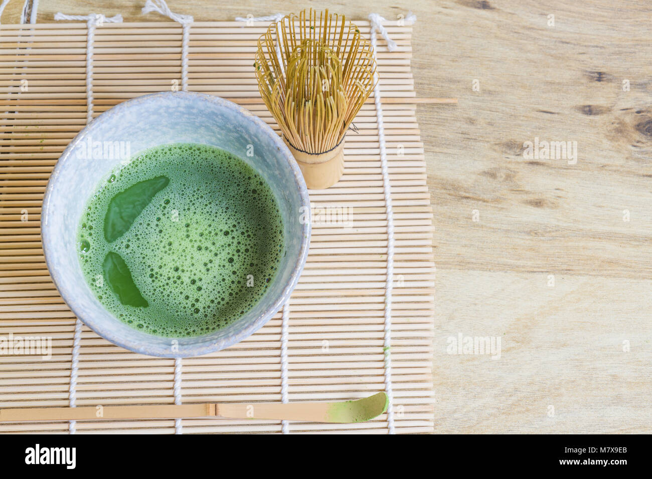 Above view of Japanese tea ceremony elements including a stone bowl of matcha green tea, bamboo whisk and bamboo - Stock Image