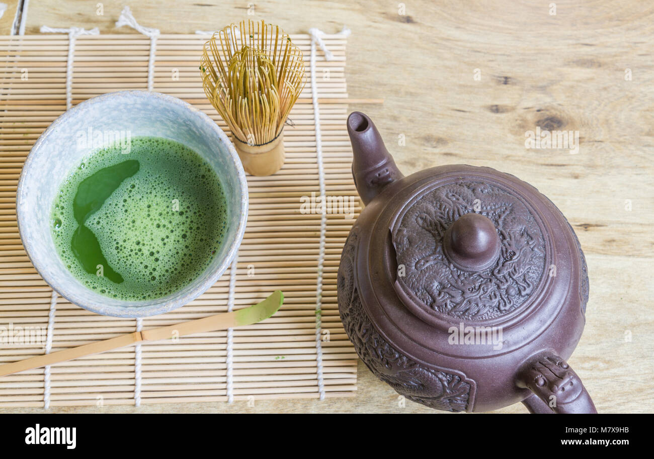 Above view of Japanese tea ceremony elements including a stone bowl of matcha green tea, bamboo whisk, scoop, and - Stock Image