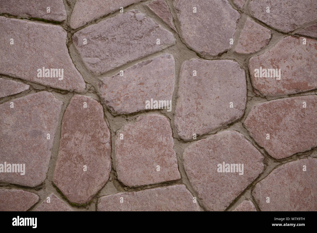 Stone wall of natural stones in different sizes, rustic stone veneer in shades of brown and beige. - Stock Image