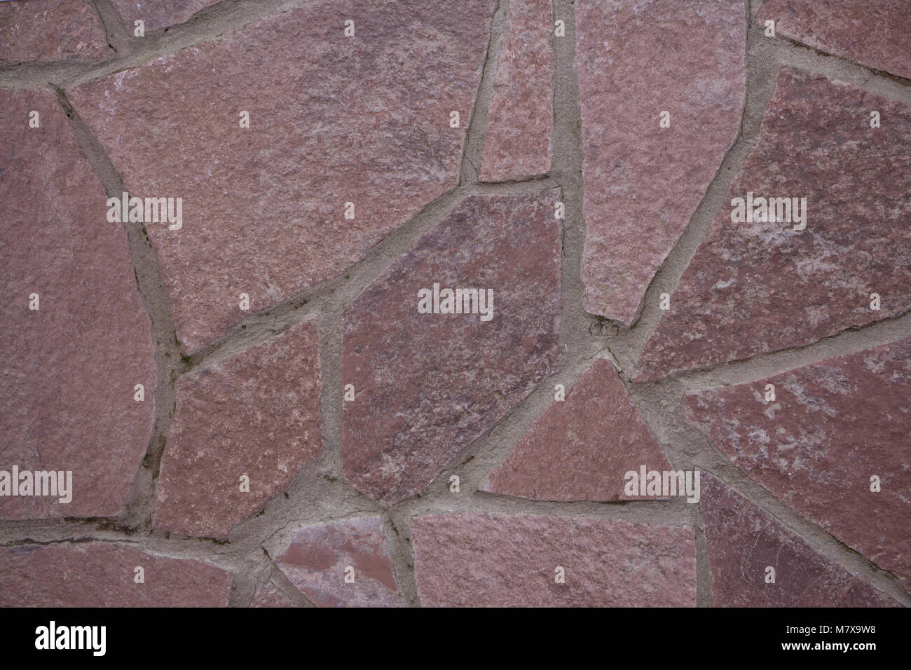 Wall stone mosaic texture for background with different rocks.Taken off the street in cloudy weather. - Stock Image