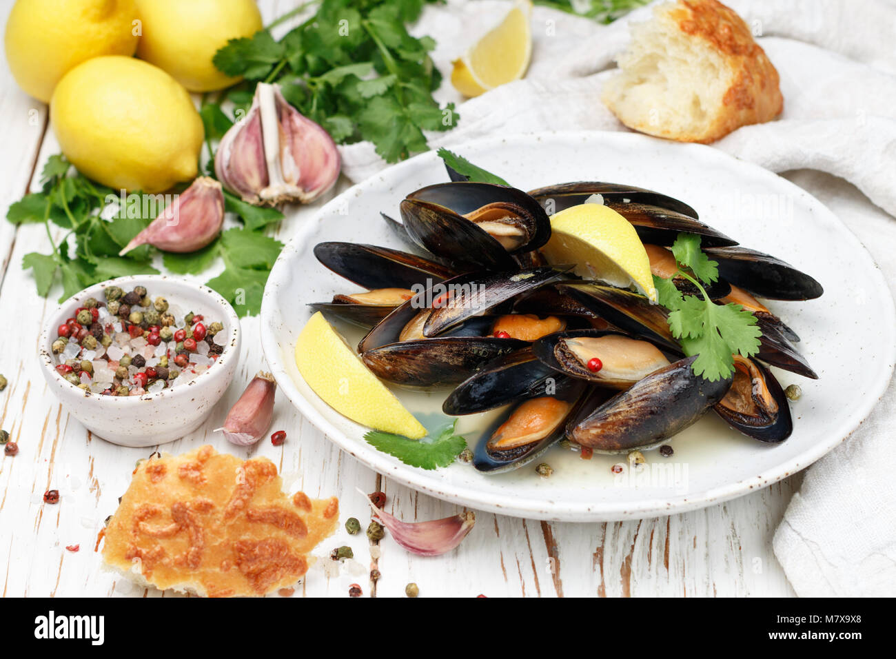 Delicious mussels in white wine with lemon, garlic, herbs and spices in a white plate. Baguette, Cilantro and pepper. - Stock Image