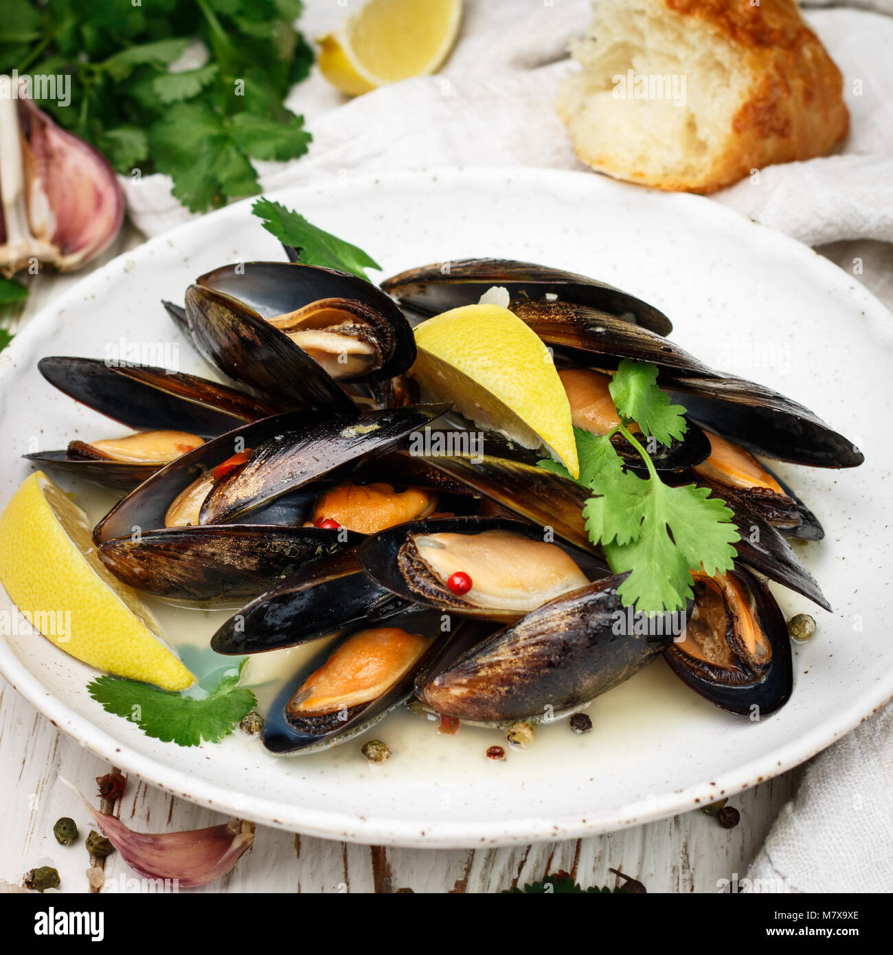 Delicious mussels in white wine with lemon, garlic, herbs and spices close up . Cilantro and pepper. Seafood. Clams - Stock Image
