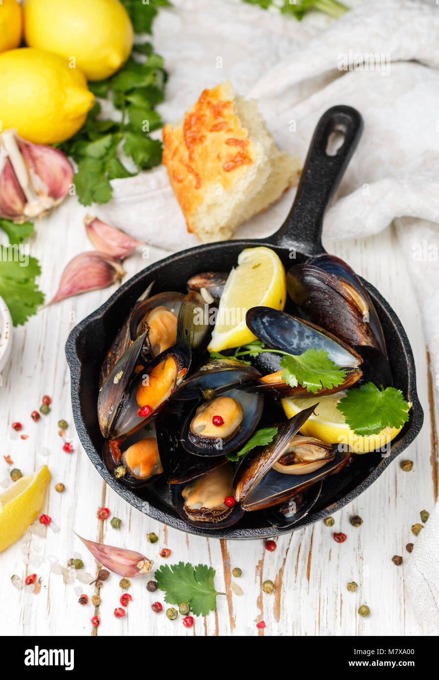 Delicious mussels in white wine with lemon, garlic, herbs and spices in a cast iron skillet . Baguette, Cilantro - Stock Image