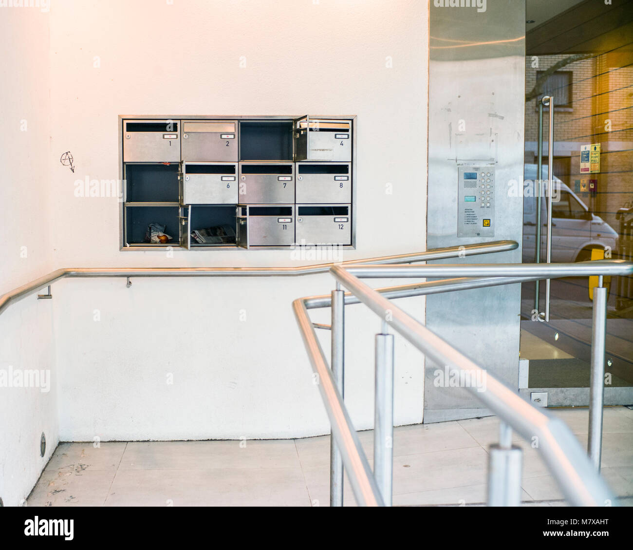 wall mounted steel mailboxes outside modern flat entrance - Stock Image
