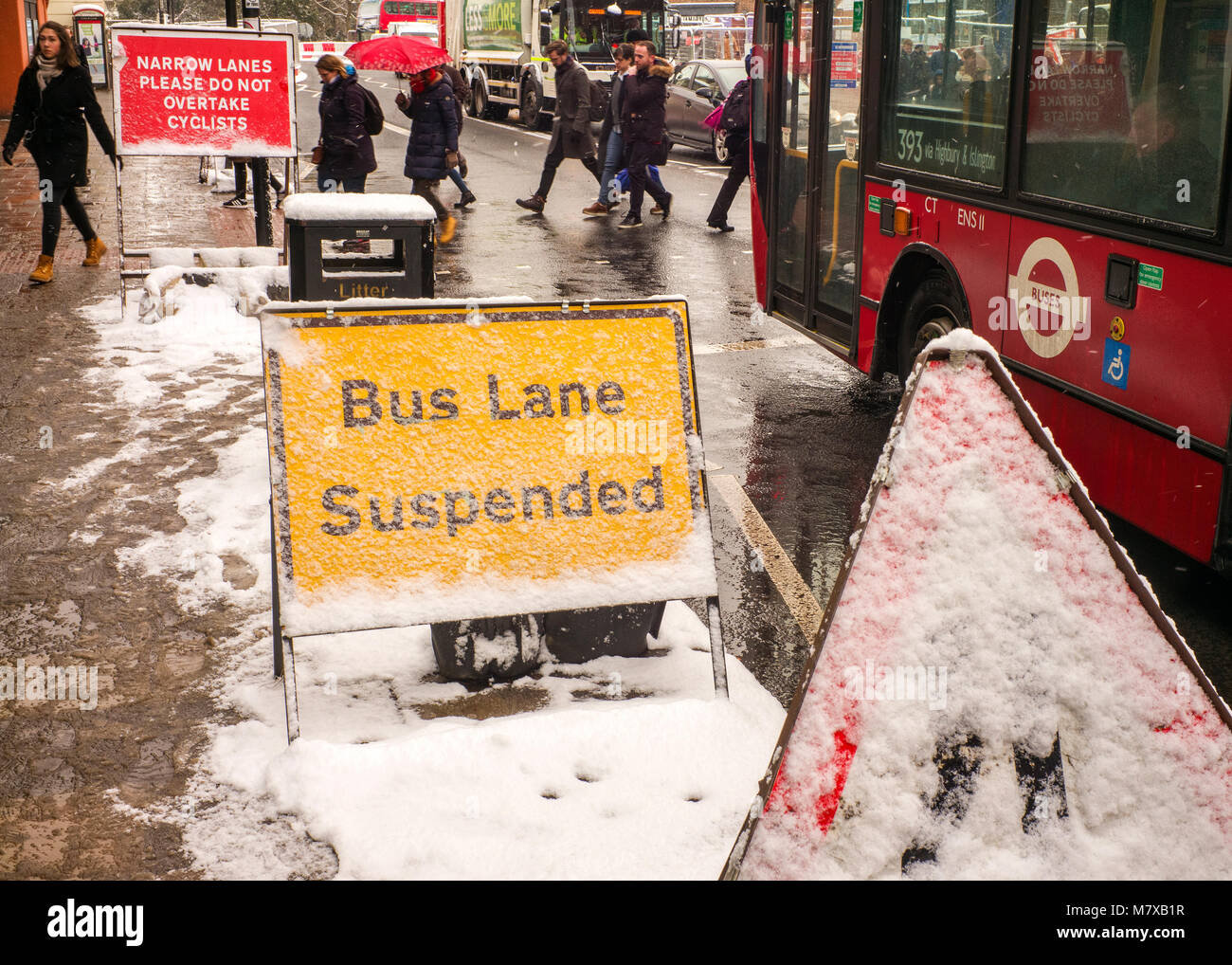 bus lane suspended sign with commuters and red bus in snow storm London - Stock Image