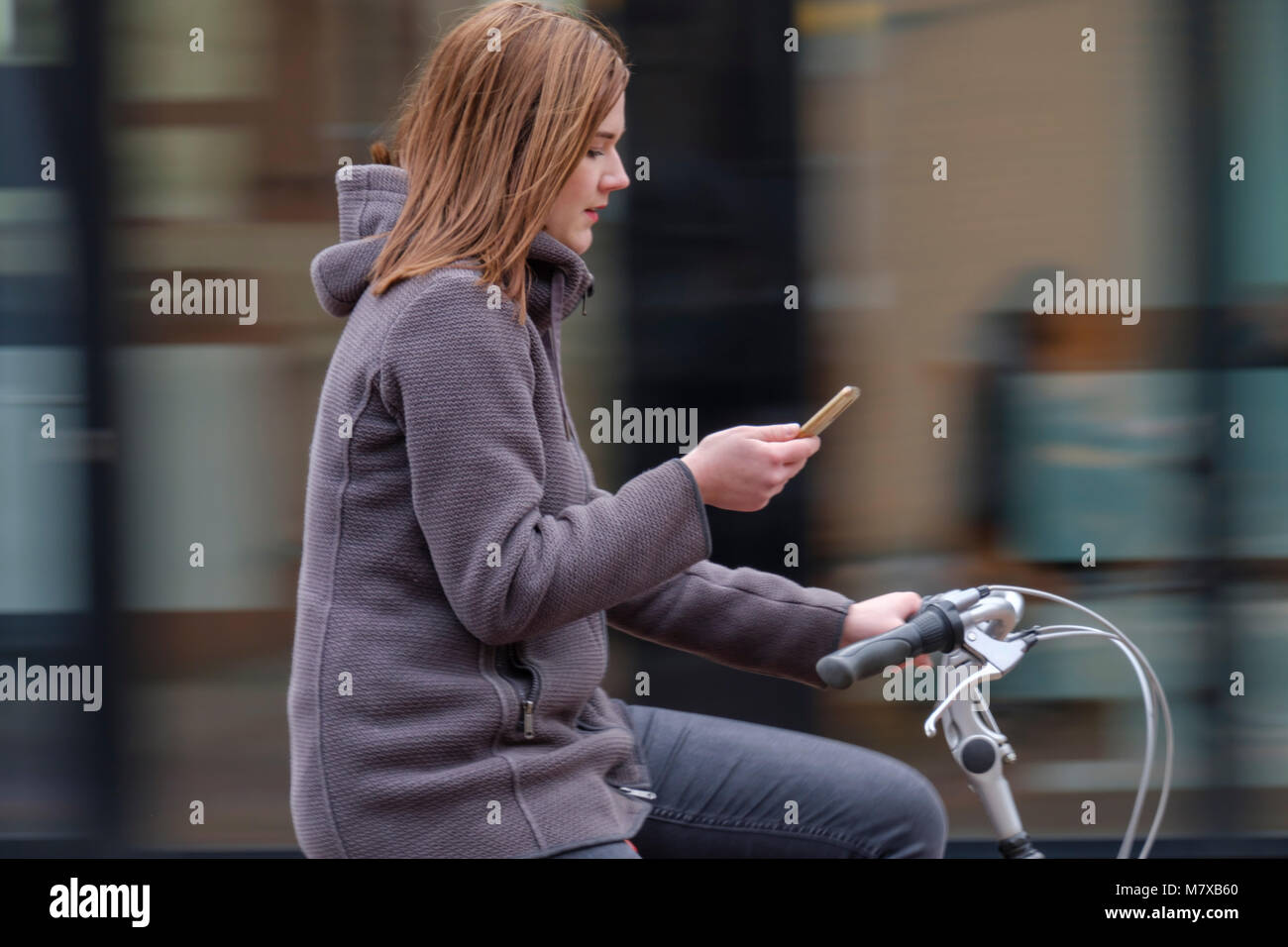 Young woman getting distracted by his smartphone while riding his bicycle around the city - Stock Image