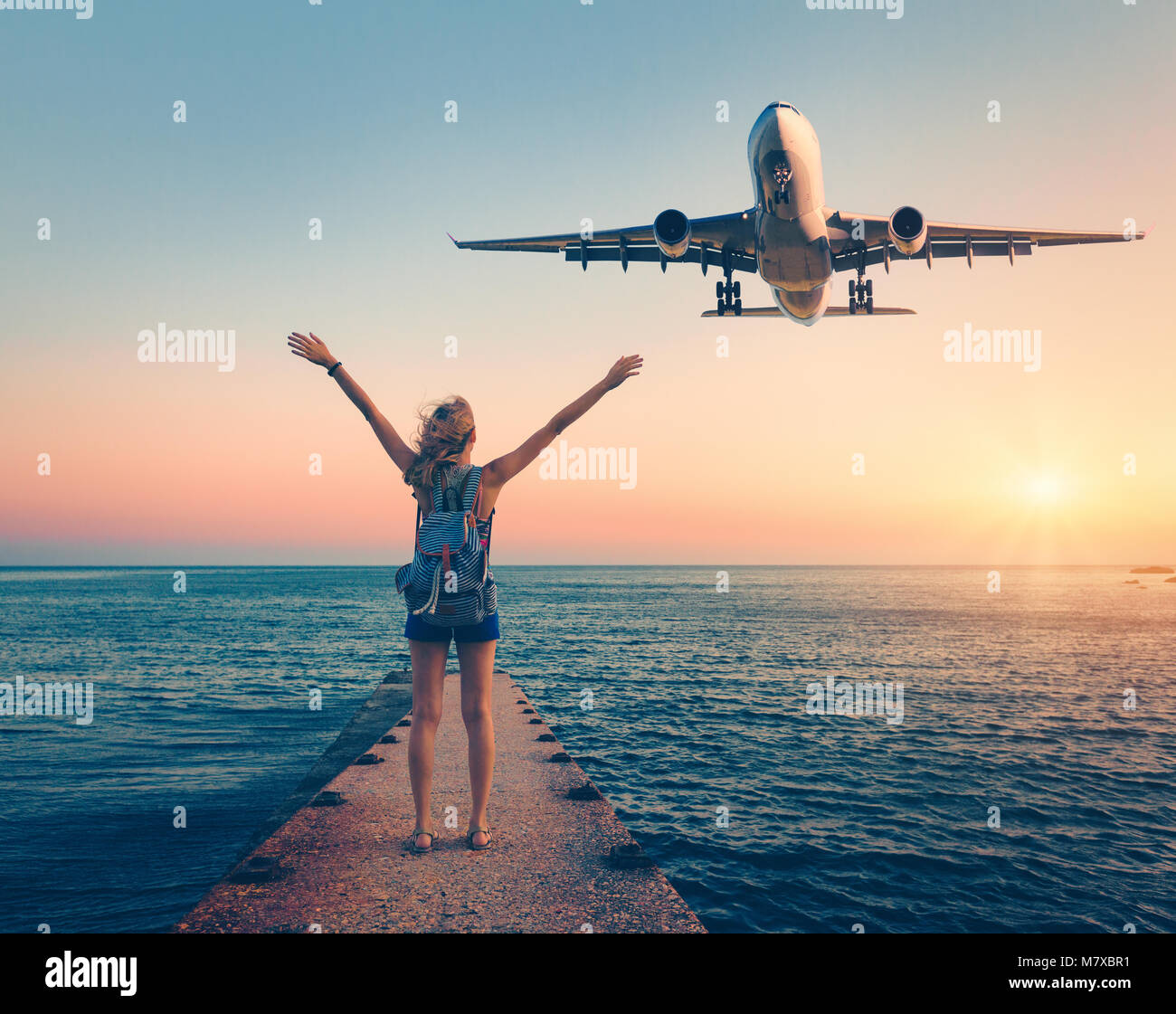 Airplane and woman at sunset. Summer landscape with girl standing on the sea pier with raised up arms and flying - Stock Image