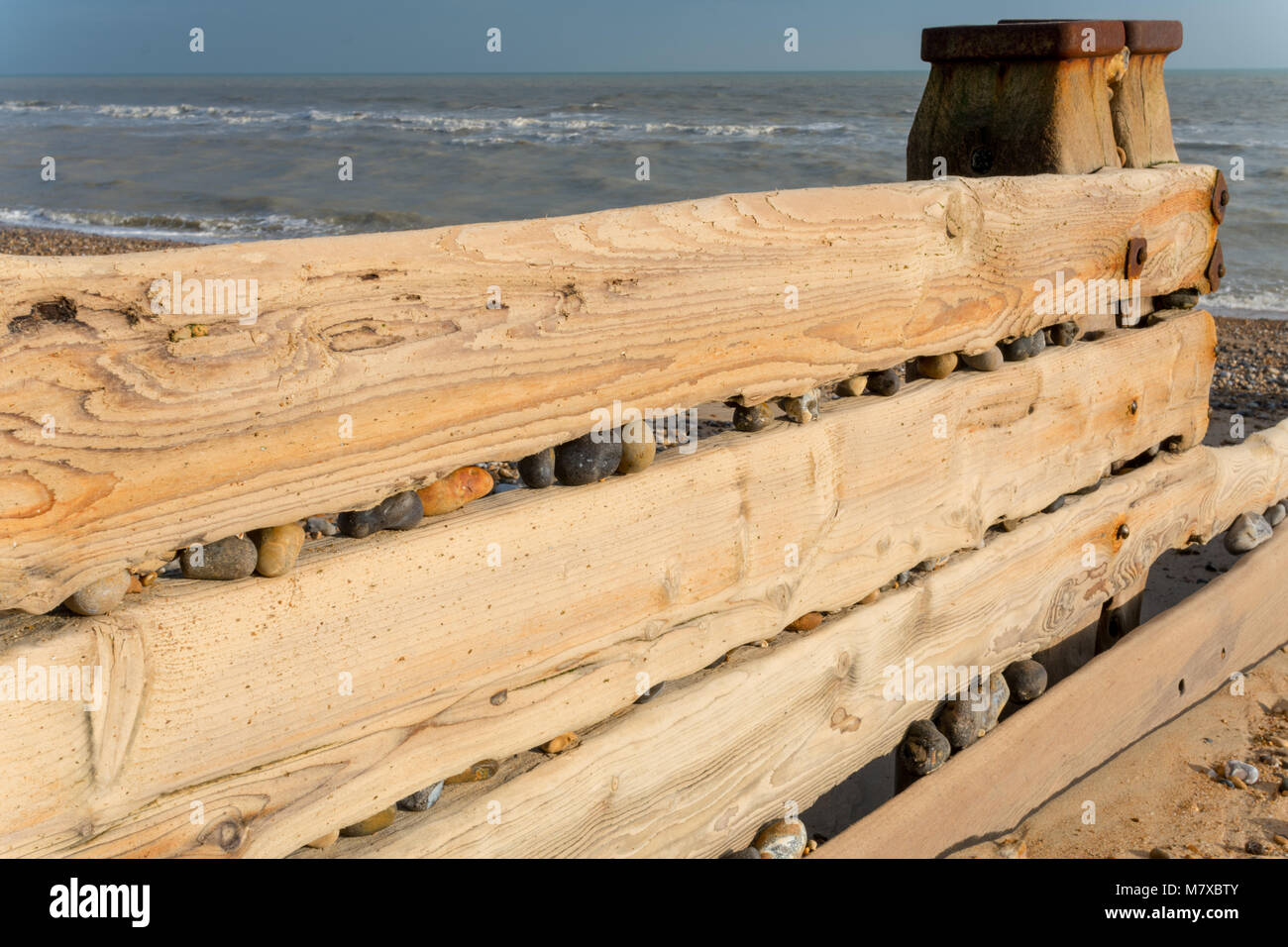 Pine groyne with pebbles jammed in the gaps by the power of the waves, on the beach at Bexhill-on-Sea, East Sussex, - Stock Image