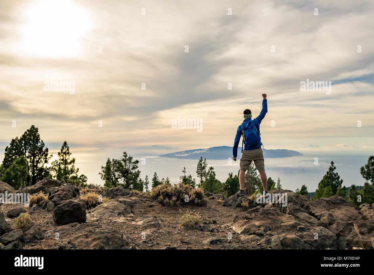 Man celebrating sunset looking at view in mountains. Trail runner, hiker or climber reached top of a mountain, enjoy - Stock Image