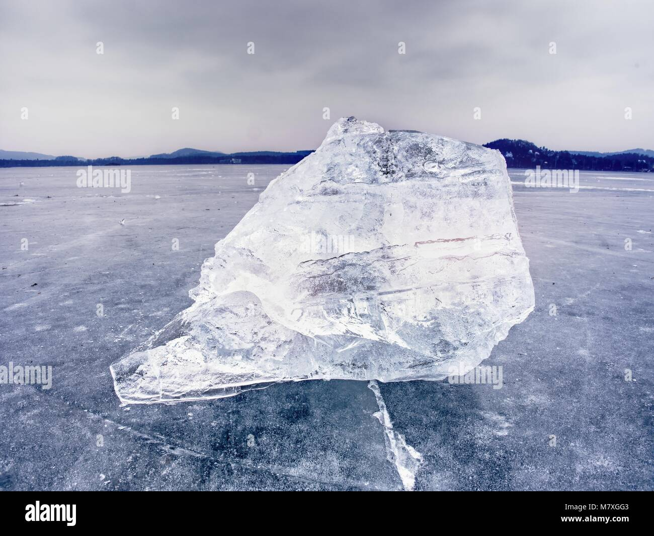 Arctic ice. A large piece of natural ice on a green blue flat ice of frozen lake, water bubbles texture. Shiny detail - Stock Image