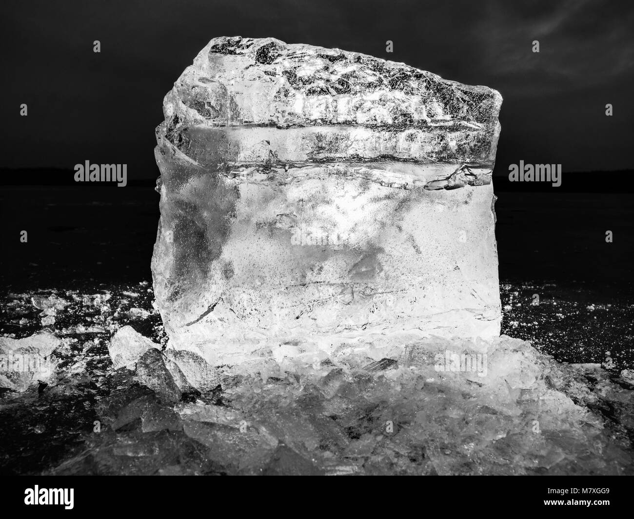 Detail view into  an ice with deep scratches and cracks. Cut floe against to evening sky and spot light. - Stock Image