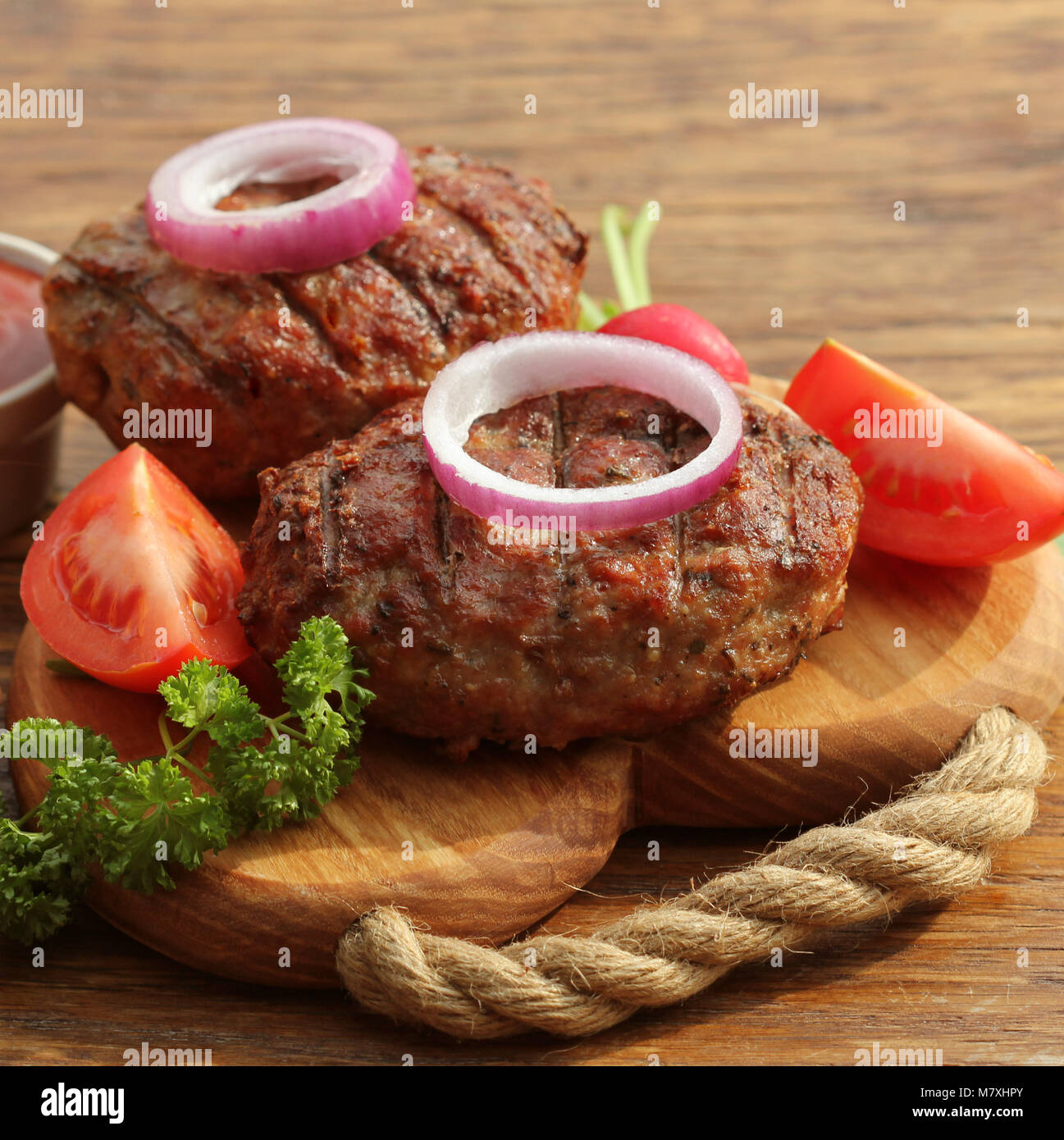 Homemade burger with beef cutlet, vegetables, onion and herbs on wooden cutting board - Stock Image