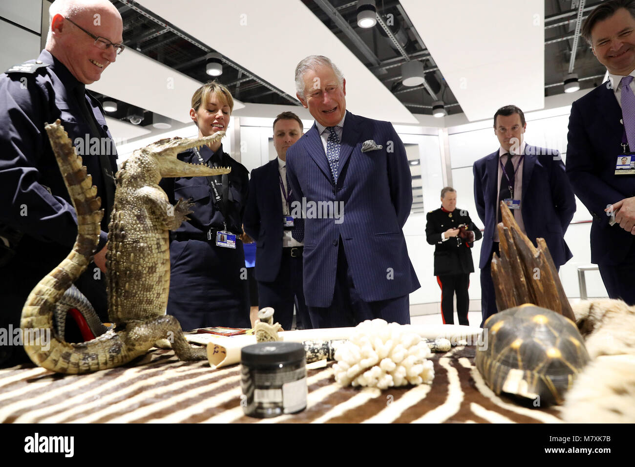 The Prince of Wales (centre) is shown items of luggage that have been confiscated during inspections by customs Stock Photo
