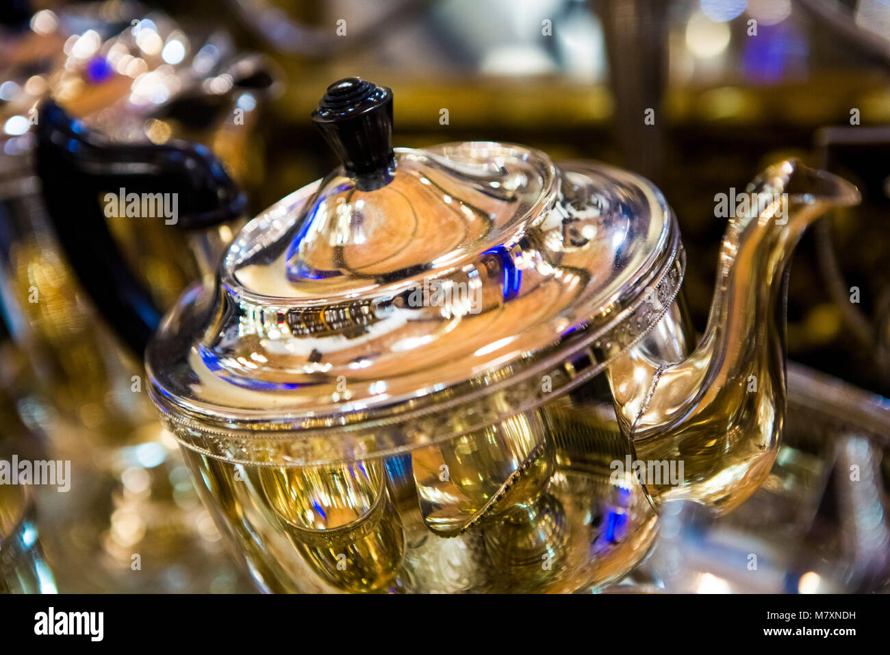 Vintage silver teapot in antiques store. - Stock Image