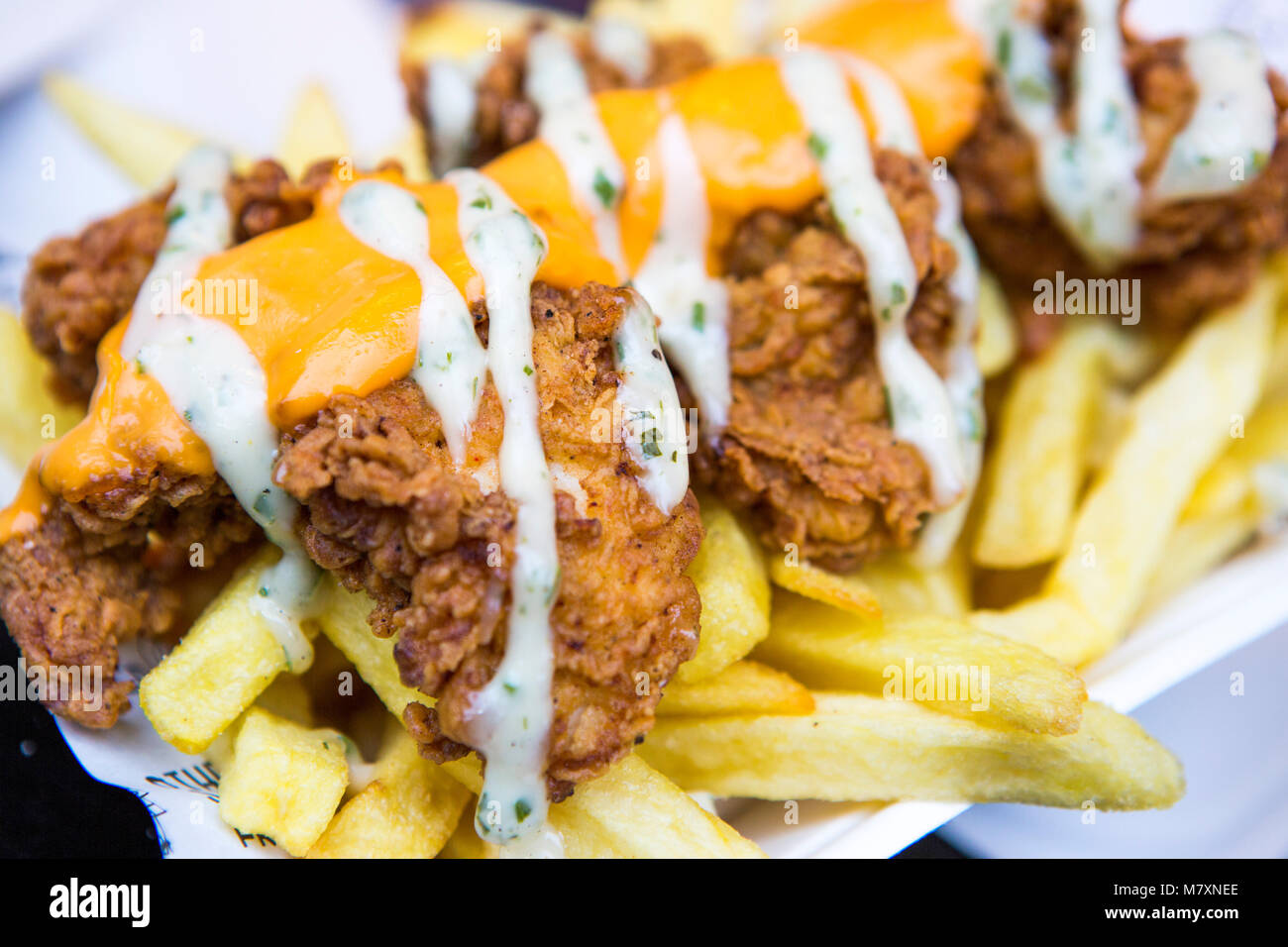 Fried chicken and chips with cheese. - Stock Image