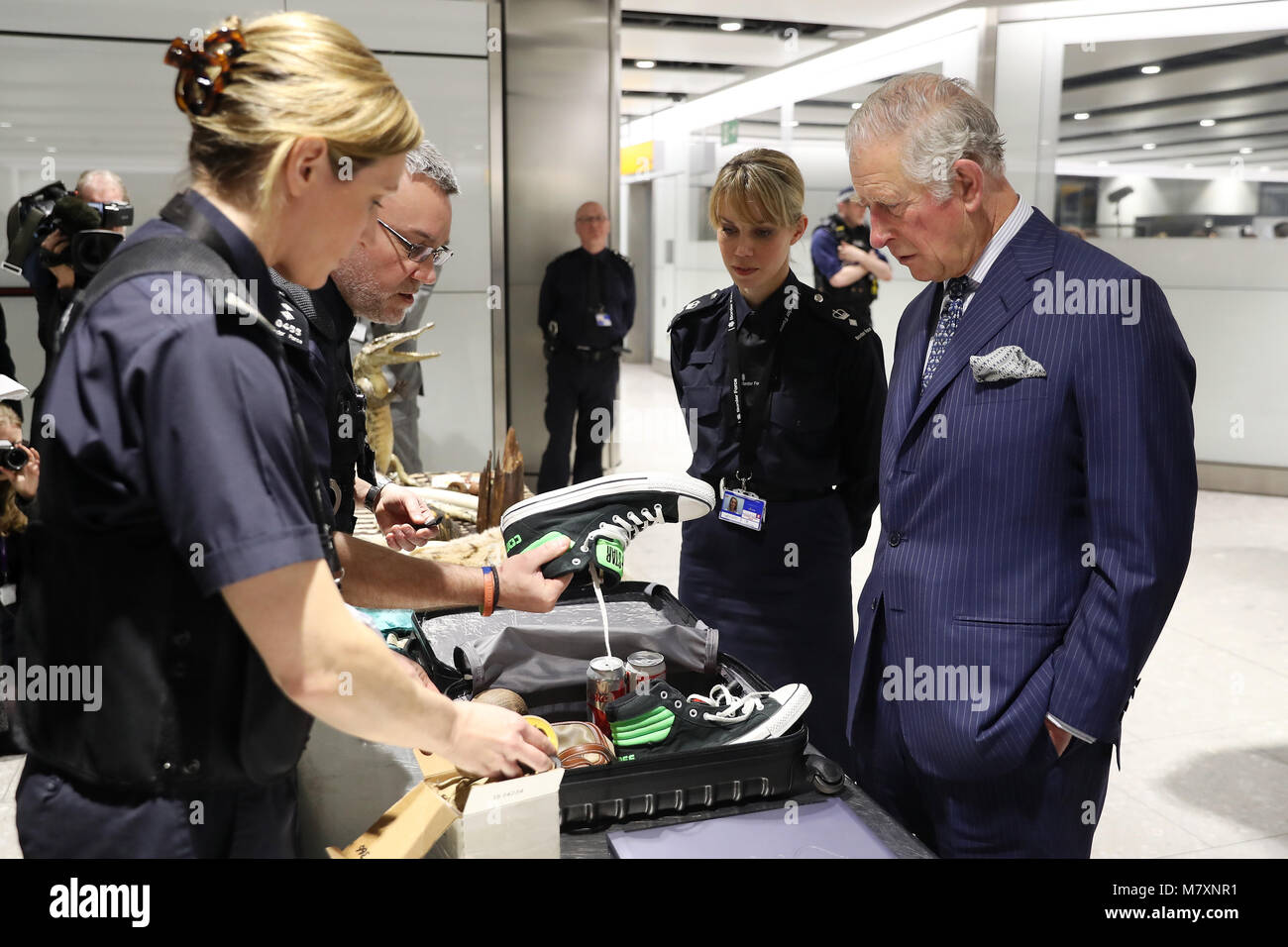 The Prince of Wales (right) is shown items of luggage that have been confiscated during inspections by customs officers Stock Photo