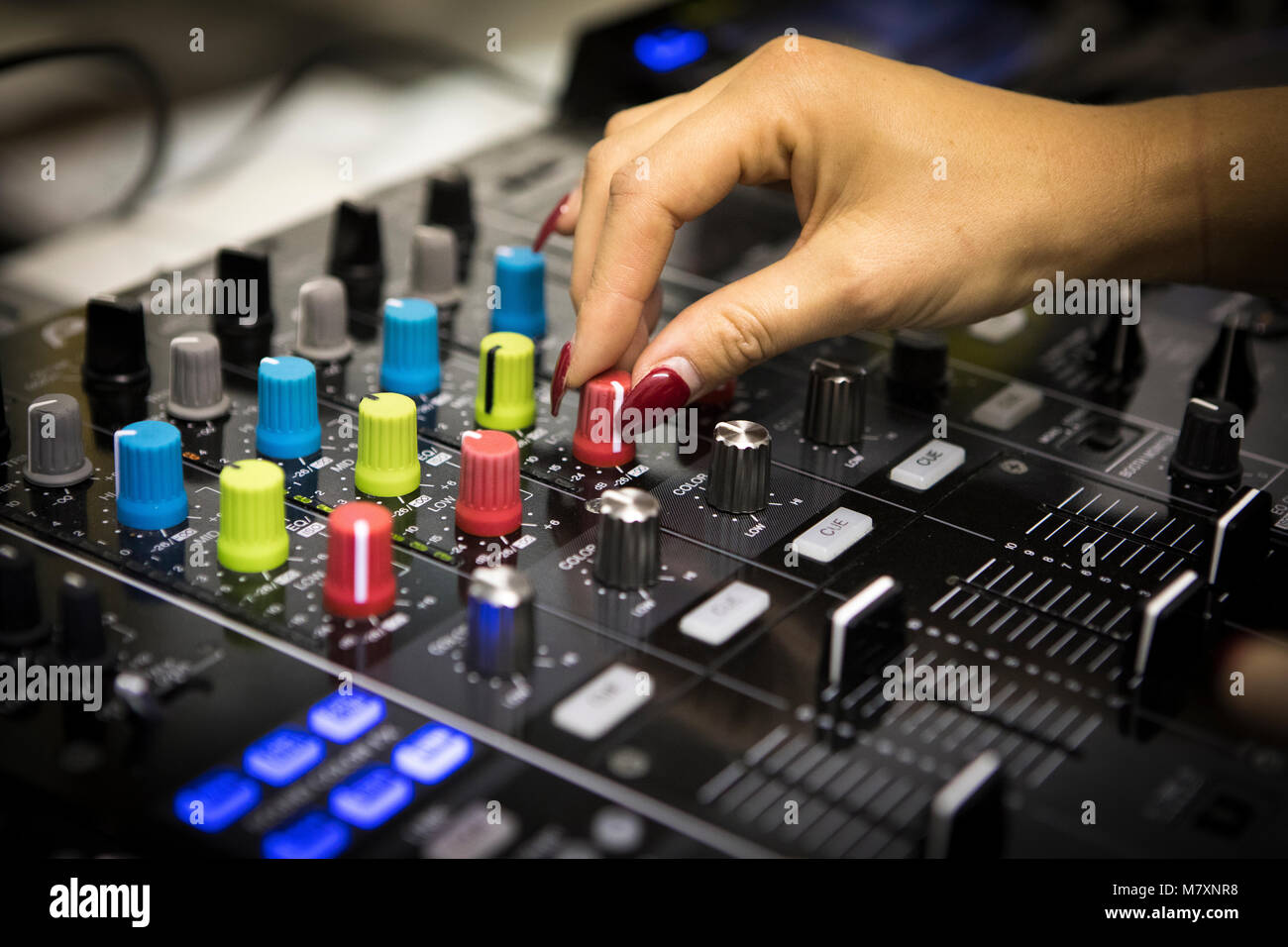 Female DJ with red fingernails on CDJ's and mixer. - Stock Image