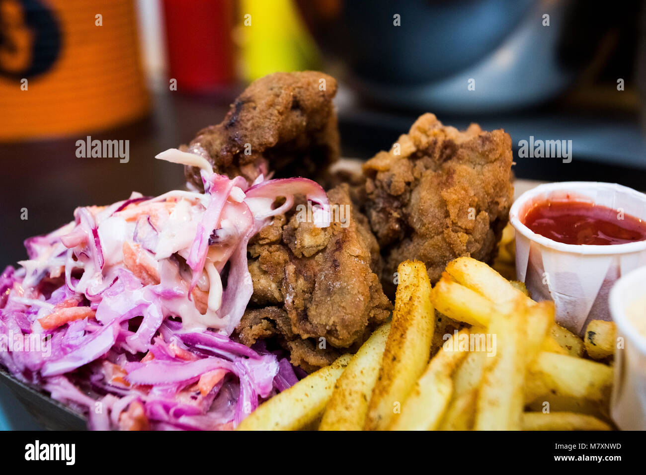Fried chicken and chips with coleslaw, dipped in mayonnaise with ketchup by man with tattoos.  Hipster street food. - Stock Image