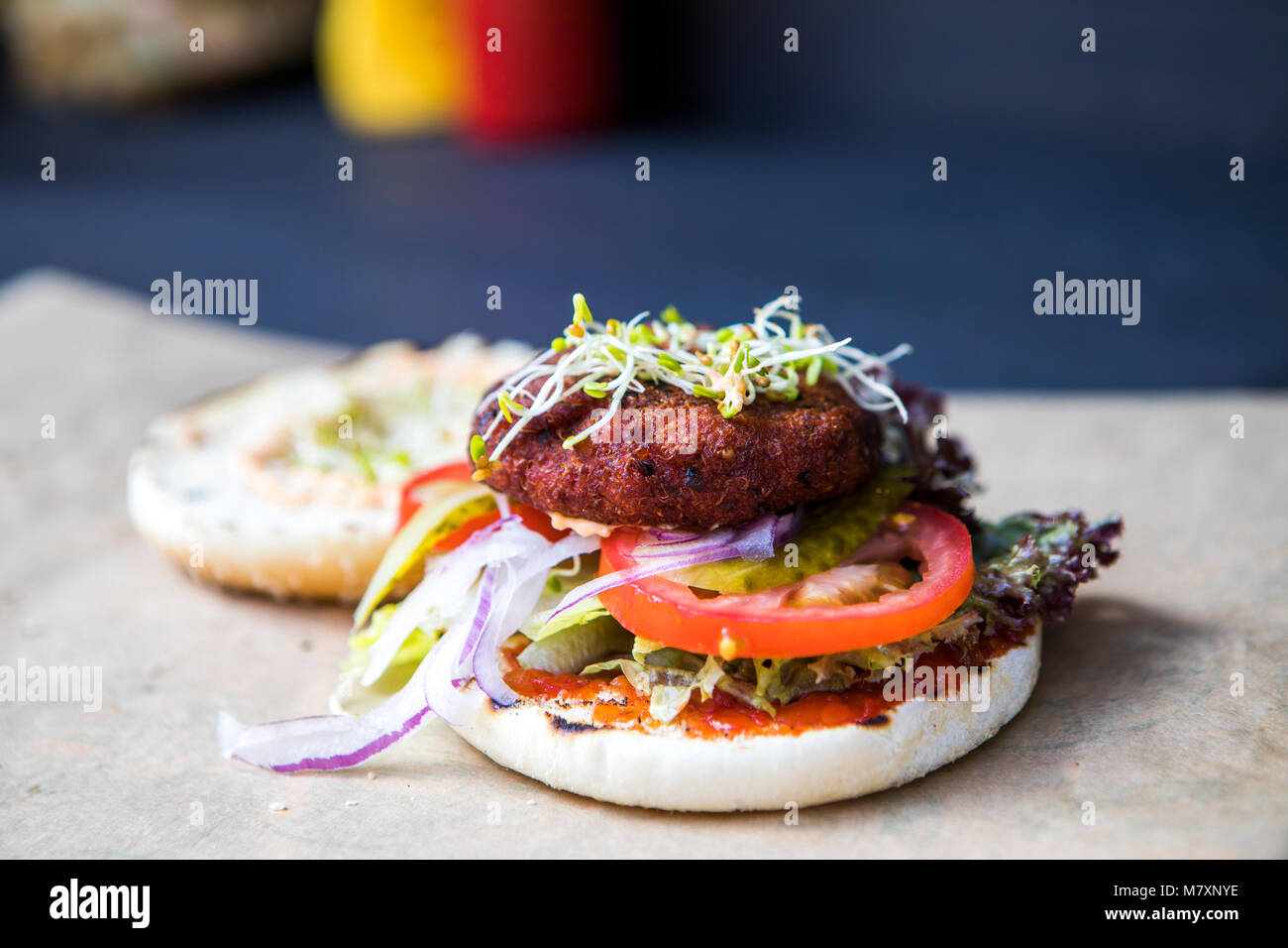 Quinoa burger, vegan street food with tomato and sprouting herbs. - Stock Image
