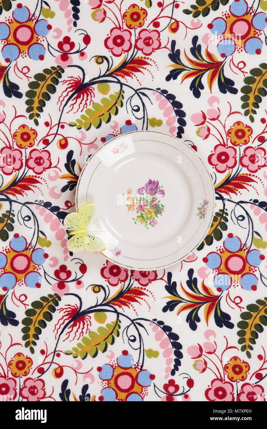 a flower plate hidden on a flowery fabric with a yellow butterfly on the edge. Camouflage game. Minimal color still Stock Photo