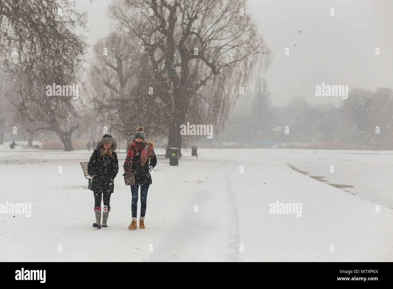 LONDON, UK: Two young women walking in white Regent's Park while it is snowing - Stock Image