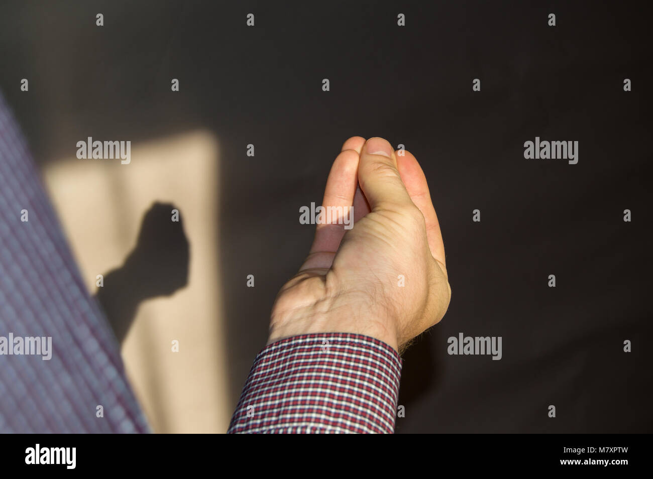 man's hand with fingers folded in a pinch, a shadow on the wall by hand - Stock Image
