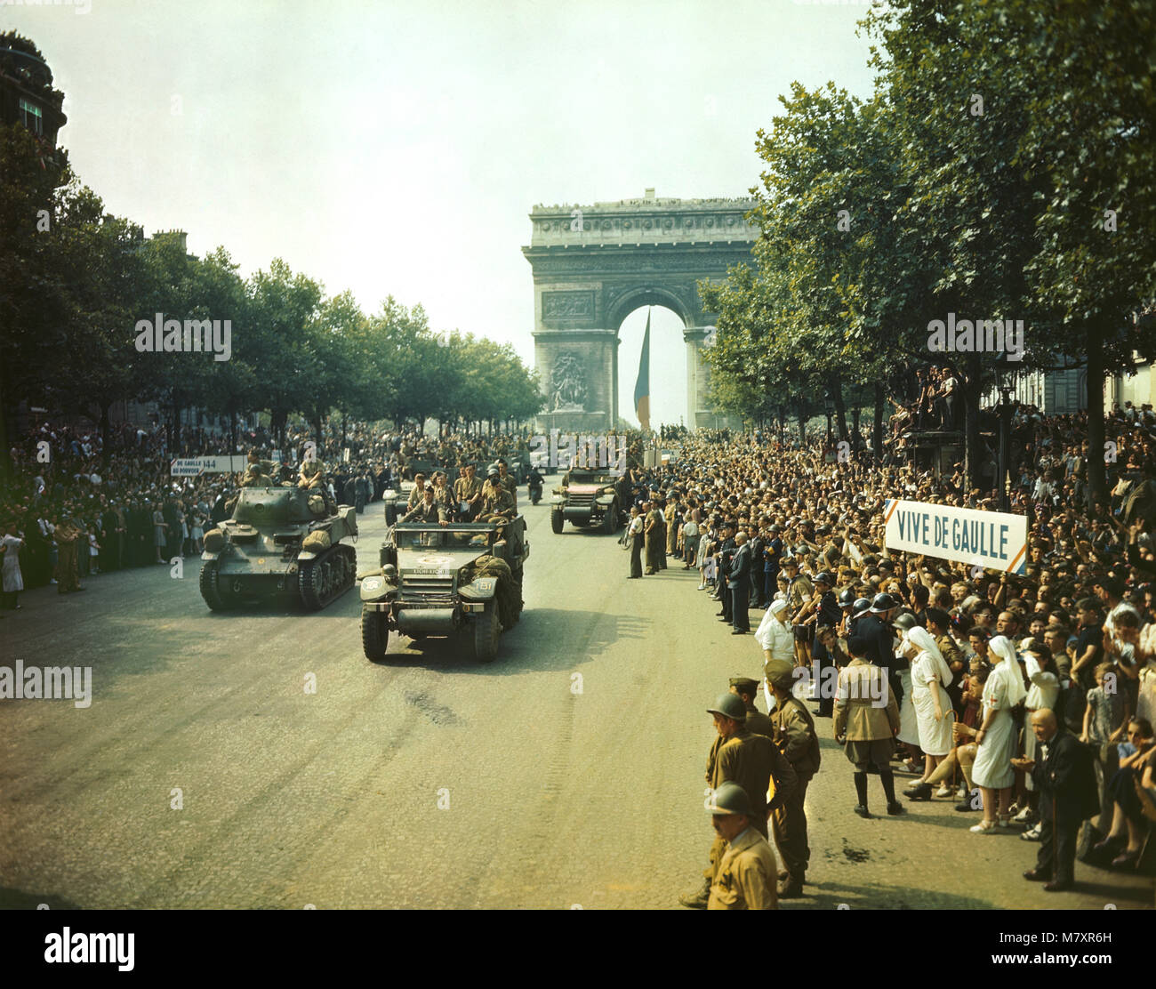 Crowds of French Patriots line Champs Elysees to view Allied Tanks and half tracks pass through the Arc du Triomphe - Stock Image