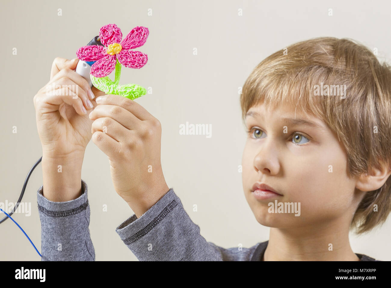 Child creating with 3D pen - Stock Image