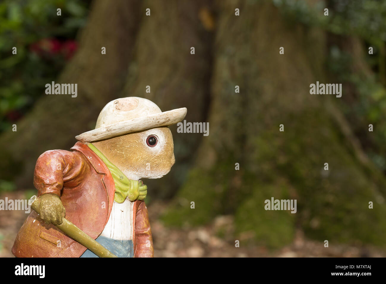 Children's woodland character busy doing the gardening! Painted sculpture set up in country woodland, base of - Stock Image