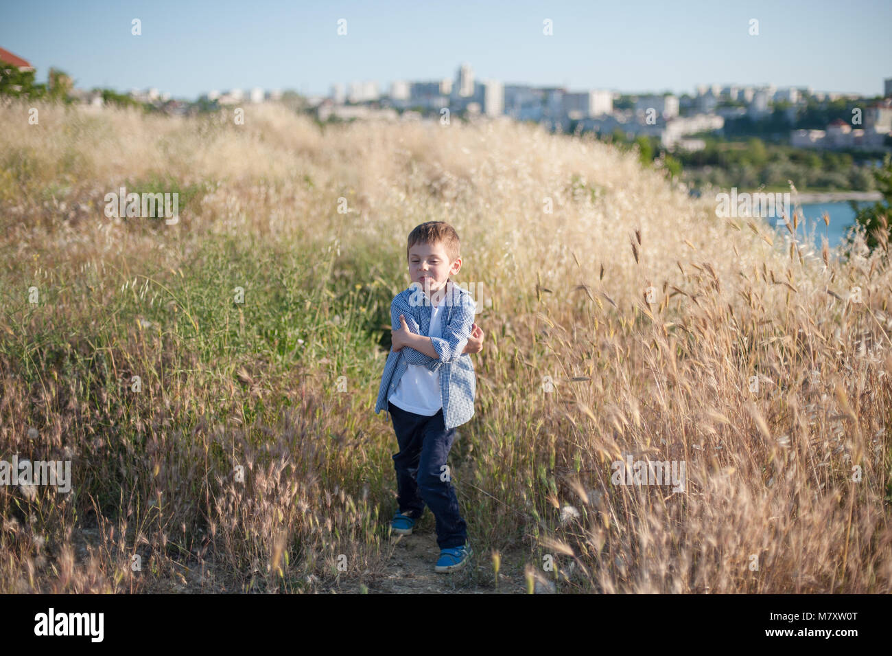 funny cute little boy grimacing standing in the middle of a field of plants - Stock Image