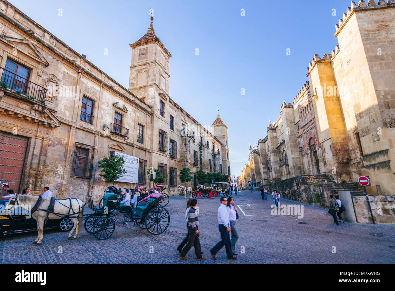 Cordoba, Andalusia, Spain : Tourists walk by the west facade of the Mosque–Cathedral and Episcopal Palace. - Stock Image