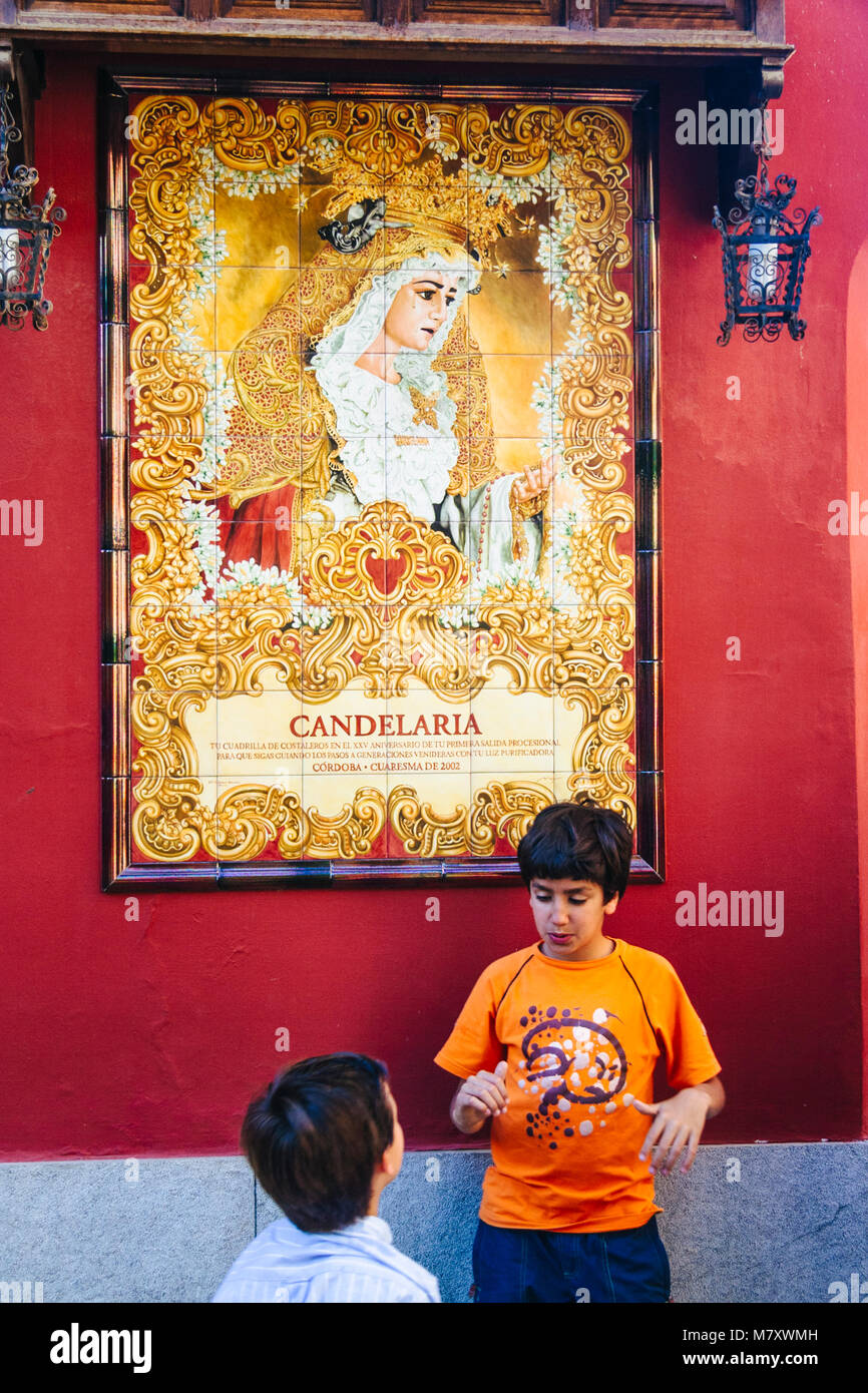 Cordoba, Andalusia, Spain. Children by a wall tile of the Virgin of la Candelaria in the historic centre of Cordoba. - Stock Image