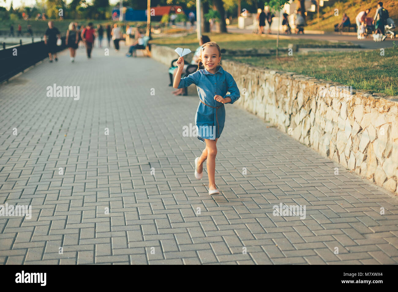 Child playing, running with toy paper airplane in the park, on gray pavage near lake in denim dress. Smiling girl - Stock Image