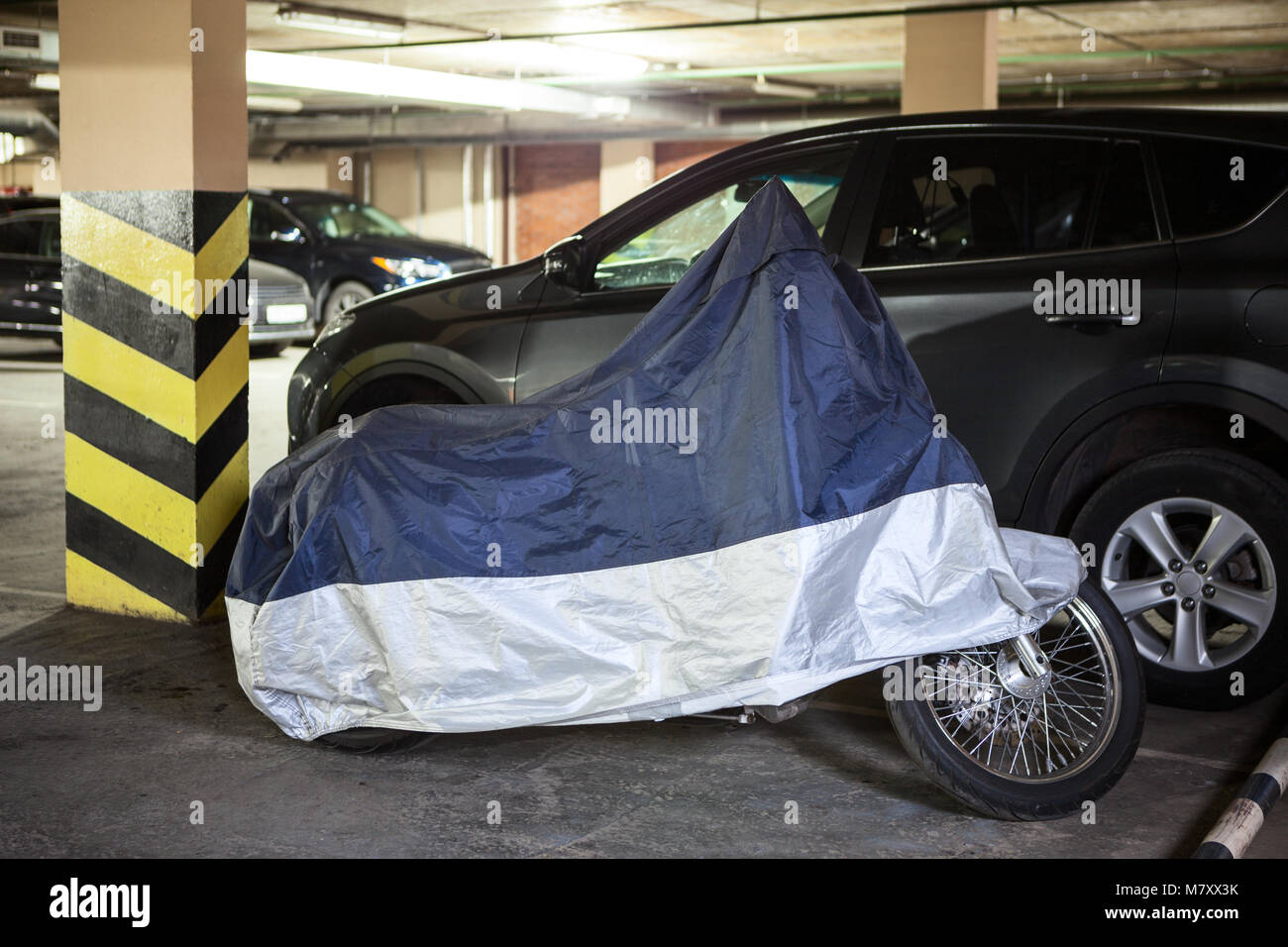 Single motorcycle is in warm underground parking garage covered with a tent - Stock Image