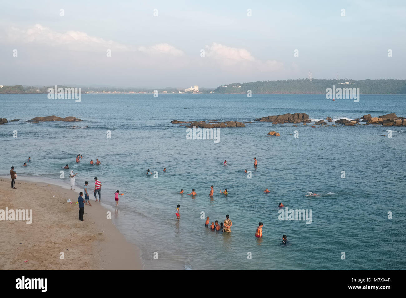 People swim in the ocean at the beach at Point Utrecht Bastion in Galle Fort in Sri Lanka - Stock Image