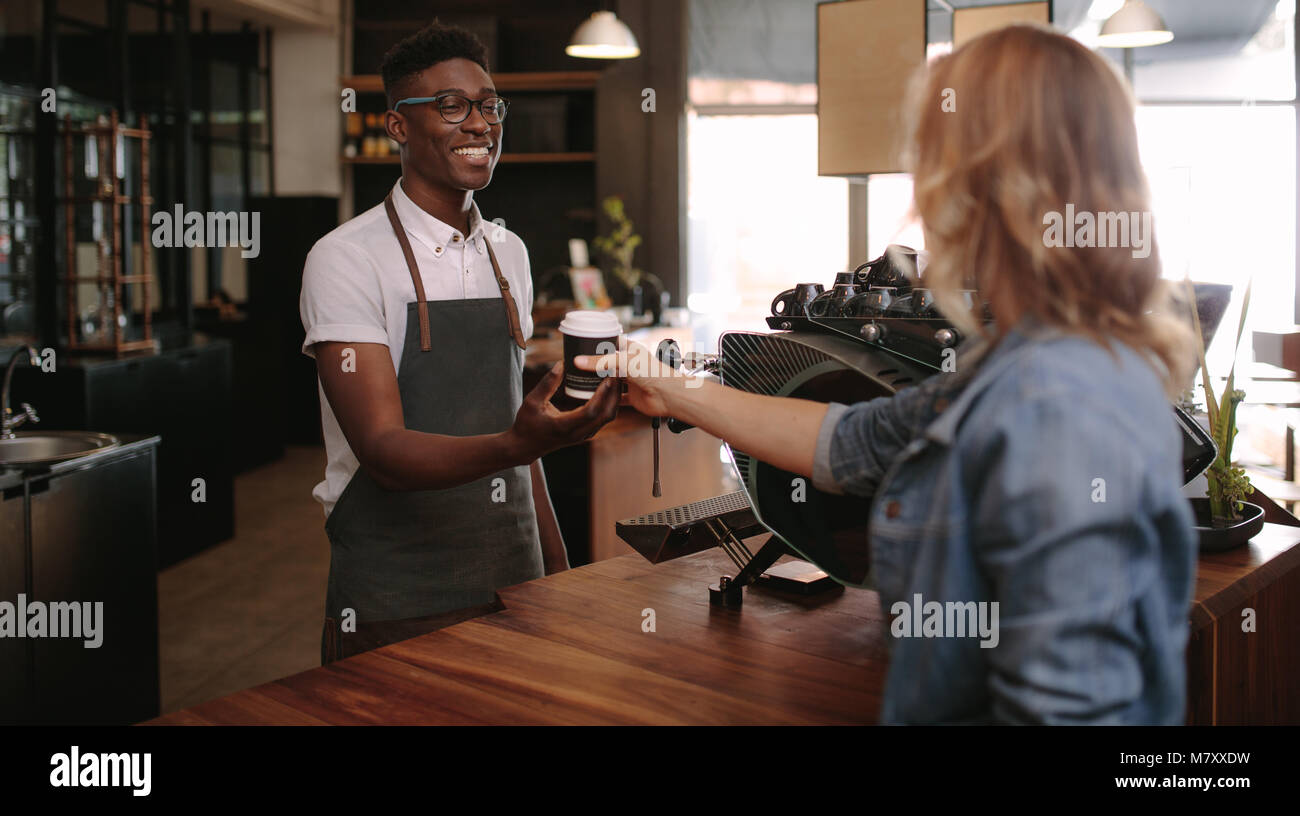 Coffee shop owner handing over a sealed coffee cup to a customer. Man serving customer with a smile at a coffee - Stock Image