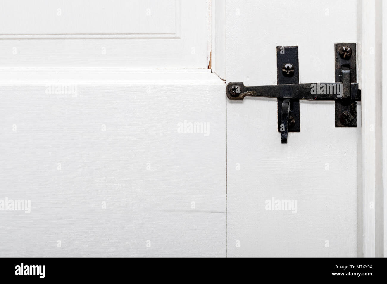 An antique black wrought iron door latch on a white painted wooded door. - Stock Image