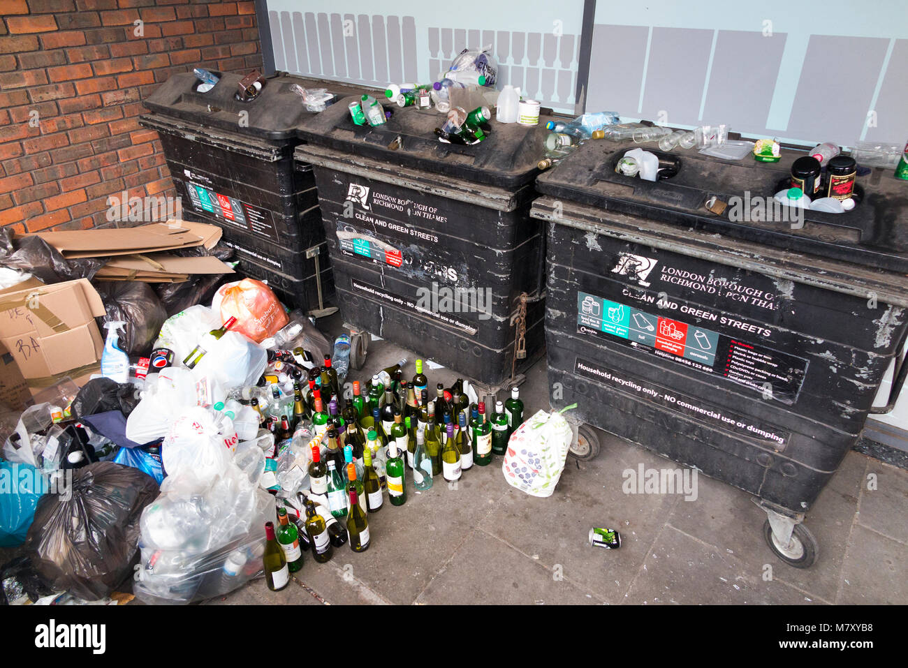 Full and overflowing / over flowing glass bottle banks and recycling skips outside a supermarket in Twickenham, - Stock Image