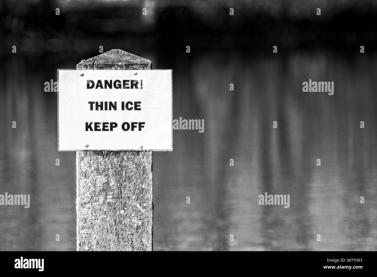 danger thin ice keep off warning sign unsafe beware alert notice winter cold freeze frozen cracked season seasonal - Stock Image