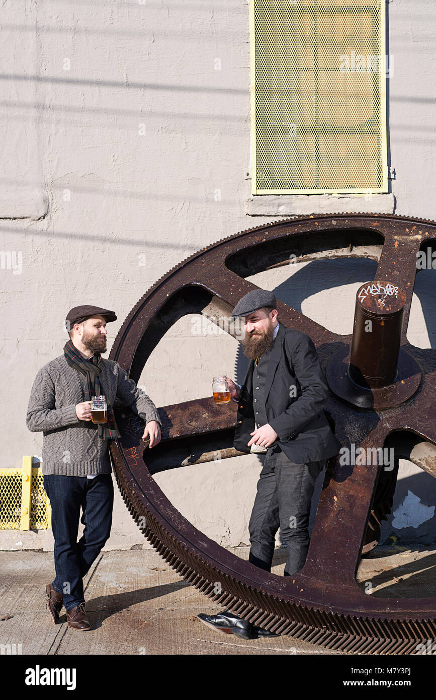 Men with beards drinking beer outside in Brooklyn standing next to a giant clock gear. - Stock Image