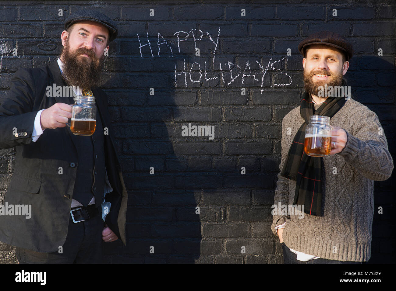 Holiday photo of two men drinking beer with Christmas greetings on the wall behind them. - Stock Image